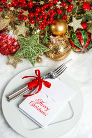 foto of dinner invitation  - festive table setting decoration with baubles golden garlands candle christmas tree and red berries - JPG