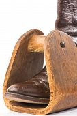 picture of caribou  - Vintage Caribou Hide Cowboy Boot in antique homemade wooden saddle stirrup against white background with copy space.