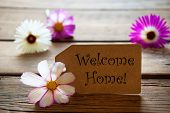 foto of purple white  - Brown Label With English Text Welcome Home With Purple And White Cosmea Blossoms On Wooden Background Vintage Retro Or Rustic Style