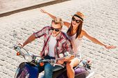 stock photo of vespa  - Top view of beautiful young couple riding scooter together while happy woman keeping arms outstretched and smiling - JPG