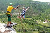 stock photo of jump rope  - Jump off a cliff with a rope on the background of mountains and sky - JPG