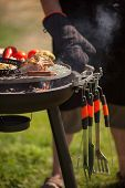 foto of barbecue grill  - Fresh meat and vegetables grilled at a summer weekend barbecue, attention on tools for a grill ** Note: Shallow depth of field - JPG