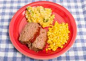 picture of meatloaf  - Sliced meatloaf corn and cheesy broccoli rice on a red plate on a blue plaid mat - JPG