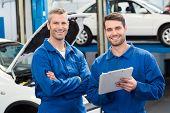 picture of garage  - Team of mechanics smiling at camera at the repair garage - JPG