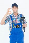 pic of plunger  - Portrait of plumber holding plunger while gesturing OK sign over white background - JPG