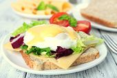 pic of benediction  - Toast with egg Benedict and tomato on plate on wooden table - JPG