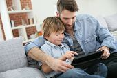 stock photo of father child  - Father with little boy using digital tablet at home - JPG
