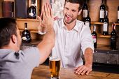 picture of bartender  - Rear view of male customer talking to bartender while sitting at the bar counter - JPG