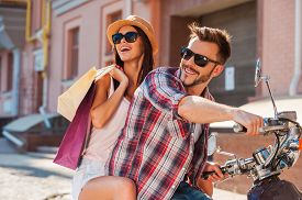 stock photo of bonding  - Side view of beautiful young couple riding scooter together while happy woman carrying shopping bags and bonding - JPG