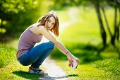 foto of no clothes  - Young happy Caucasian blonde woman with coffee beverage sitting in park wearing casual clothes and jeans no make - JPG