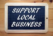 stock photo of slating  - The phrase Support Local Business in white text on a slate blackboard - JPG