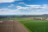 foto of cultivator-harrow  - Aerial view of the the tractor harrowing the large brown field in spring season - JPG