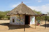 stock photo of threshing  - Traditionally decorated hut in the tribal village on the desert in India in the Gujarat state - JPG