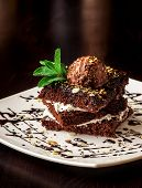 pic of brownie  - Chocolate brownie cake with a scoop of ice cream with a mint leaf on a white plate - JPG