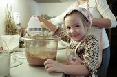 picture of cake-mixer  - Happy little girl mixing dough for a birthday cake being independent and proud helping mum in the kitchen - JPG
