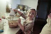 stock photo of cake-mixer  - Happy little girl mixing dough for a birthday cake being independent helping mum in the kitchen - JPG