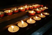 stock photo of altar  - lighted candles in the church above the altar  - JPG