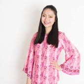 image of southeast asian  - Portrait of happy Southeast Asian woman in pink batik dress standing on plain background - JPG