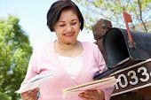 stock photo of mailbox  - Senior Hispanic Woman Checking Mailbox - JPG