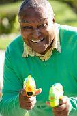 image of pistol  - Senior Man Shooting Water Pistols - JPG