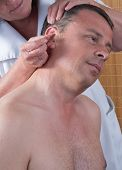 stock photo of pointed ears  - Woman acupuncturist prepares to tap needle around ears of man - JPG