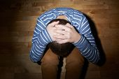 image of child abuse  - Child abuse composition of a frightened young boy sitting on the wooden floor in a light of a flashlight circle - JPG