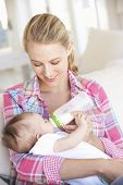 foto of feeding  - Young Mother With Baby Feeding On Sofa At Home - JPG
