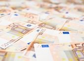 picture of fifties  - Surface covered with multuple fifty euro bank note bills as a background composition with a shallow depth of field - JPG