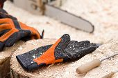 image of chainsaw  - Close up of safety gloves used for cutting wood with chainsaw - JPG