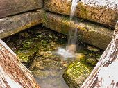 stock photo of groundwater  - Well with pure spring water in a holy place - JPG