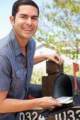 stock photo of mailbox  - Hispanic Man Checking Mailbox - JPG