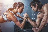 Athlete muscular sportsmen man and woman with hands clasped arm wrestling challenge between a young poster