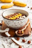 stock photo of chocolate spoon  - Chocolate hazelnut smoothie bowl topped with sliced banana - JPG