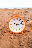 image of analog clock  - Classic Analog Clock In The Sand On The Rock Desert - JPG