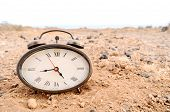 picture of analog clock  - Classic Analog Clock In The Sand On The Rock Desert