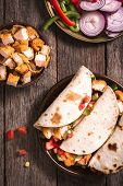 picture of sandwich wrap  - Tortilla wrap sandwiches with fried chicken and vegetables on wooden background selective focus - JPG