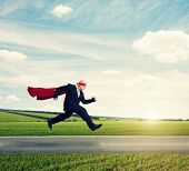 stock photo of running-late  - senior businessman wearing like superhero very fast running on the road over green fields and blue sky - JPG