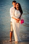 picture of barefoot  - brunette bride and handsome groom barefoot stand at sand beach at dawn - JPG