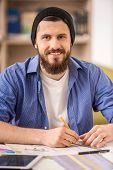 picture of draft  - Smiling man dressed casual sitting at the table and drawing draft - JPG