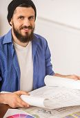 pic of draft  - Male designer dressed casual sitting at the table and holding draft at office - JPG