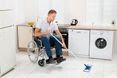 image of disability  - Disabled Man On Wheelchair Cleaning Floor With Mop In Kitchen Room - JPG