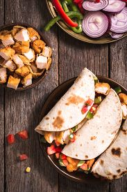pic of sandwich wrap  - Tortilla wrap sandwiches with fried chicken and vegetables on wooden background selective focus - JPG