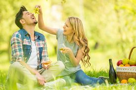 picture of eat grass  - Young beautiful couple dressed casual having picnic in park eating grape and drinking wine - JPG