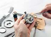 Постер, плакат: Watchmaker hands repairing mechanism of old watch closeup