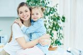 Cheerful and affectionate mother and daughter in embrace spending time at home poster