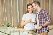 Young affectionate man standing close to his wife while having morning tea in the kitchen poster