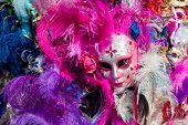 Ornated carnival mask among colorful feathers in Venice, Italy. poster