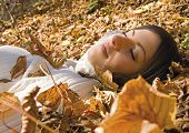 pretty girl lying in autumn-leaves