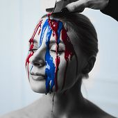 Paint On The Female Face, Close-up. Flows Of Red And Blue Paint On The Face. Artistic Portrait Of A poster