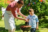 food, people and family time concept - father and son cooking meat on barbecue grill at bbq party in poster